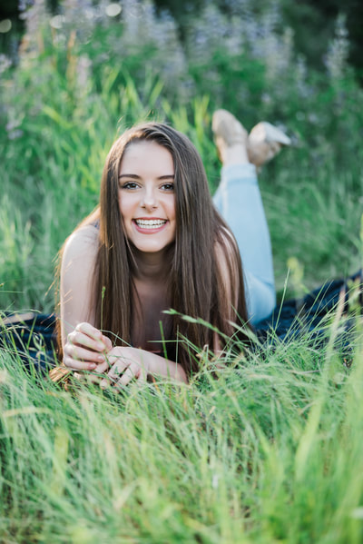 Clackamas photographer takes a photo of a girl laying in a field