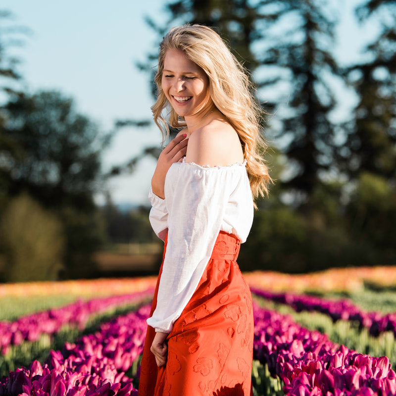 Happy Valley Photographer takes a photo of high school senior girl laughing in a field of tulips