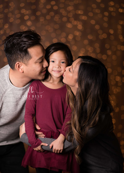 Happy Valley Photographer takes a photo of parents kissing preschooler